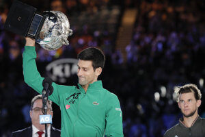 Novak Djokovič s trofejou pre víťaza Australian Open, v pozadí finalista Dominic Thiem.