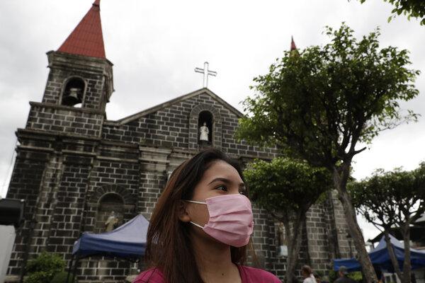 Žena s ochranným rúškom na tvári kráča pred kostolom vo filipínskom Mandaluyonge.
