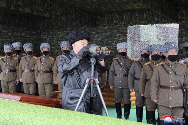 Kim pozoruje vojenské cvičenie. Vojaci za ním majú rúšky, on nie.