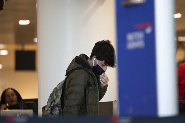 Muž s ochranným rúškom na letisku Brussels International Airport 12. marca 2020.