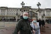 Pár pred Buckinghamským palácom v Londýne nosí rúška.