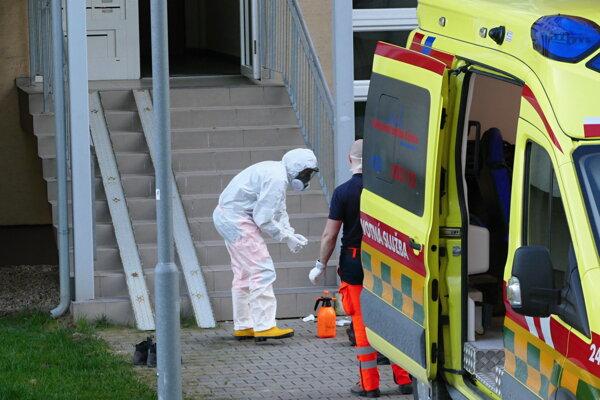 Zdravotník v ochrannom odeve počas dezinfekcie pred sídliskovým panelákom po odobratí vzoriek od ľudí s podozrením na nový koronavírus.
