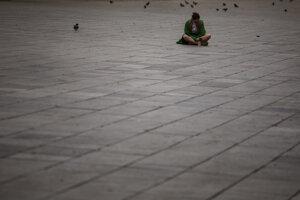 Žena sedí na prázdnom námestí v španielskej Barcelone.