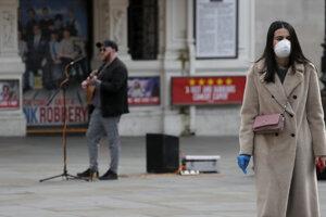 Žena kráča s ochranným rúškom na Piccadilly Circus v anglickom Londýne.