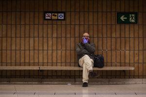 Muž si zakrýva ústa a nos počas čakania na vlakovej stanici 17. marca 2020 v Barcelone.