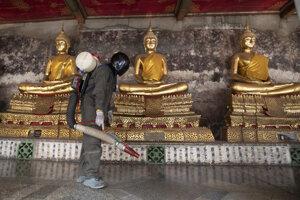 Zamestnanec v ochrannom odeve dezinfikuje ako prevenciu pred šírením nového koronavírusu vnútorné priestory budhistického chrámu Wat Suthat v thajskom Bangkoku.