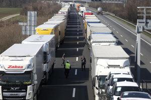 Kolóna kamiónov stojí na diaľnici blízko hranice medzi Rakúskom a Maďarskom neďaleko obce Bruck an der Leitha v Rakúsku 18. marca 2020.