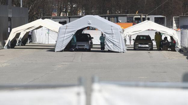 Zdravotníci pracujú na výstavisku Theresienwiese, ktoré slúži ako odberné miesto na testovanie nového koronavírusu u ľudí priamo z okna auta (systém drive-through) v Berlíne.