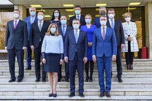 Spoločná fotografia členov vlády v ochranných rúškach počas 203. rokovania vlády.