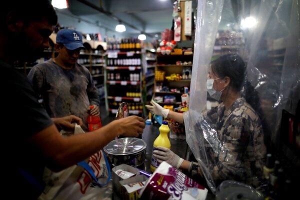 Predavačka v supermarkete pracuje pre koronavírus za závesom. Buenos Aires, 16. marec 2020.