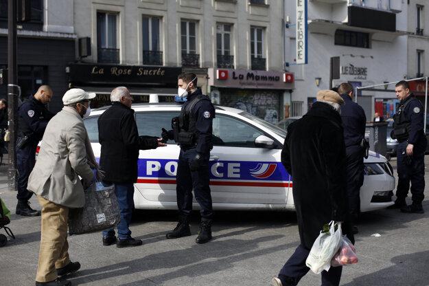 Policajti kontrolujú ľudí pred vstupom na trh v Paríži.