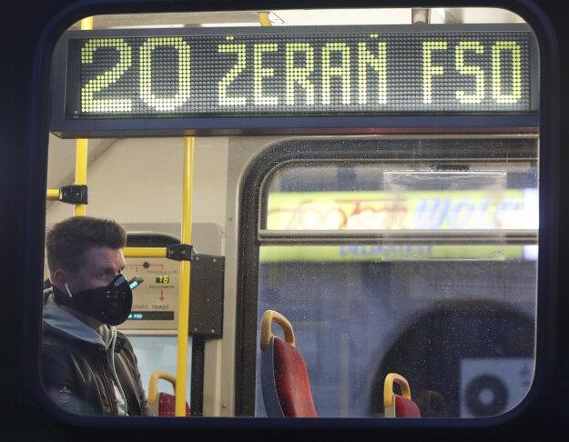 Cestujúci s ochranným rúškom na tvári sedí v električke vo Varšave.