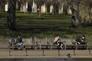 Ľudia sedia oddelene na lavičkách v parku v Londýne.