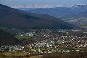 Okrajové časti mesta Rožňava, vzadu uprostred Rožňavská Baňa, vpravo dole sú kasárne. V pozadí za Volovskými vrchmi sa vypínajú Vysoké Tatry.