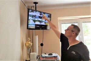 Starosta Rakova Patrik Antal pri monitore, kde sa zobrazujú záznamy z kamier.