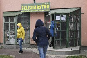 Ľudia čakajú v rade pred železiarstvom v Košiciach.
