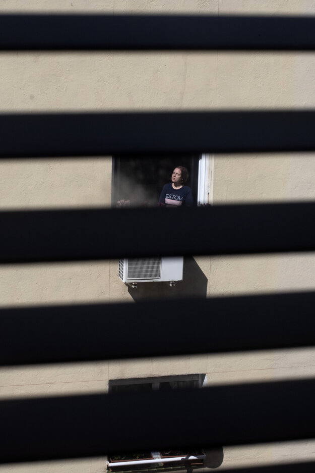 Žena stojí v okne a slní sa počas karantény v Madride.