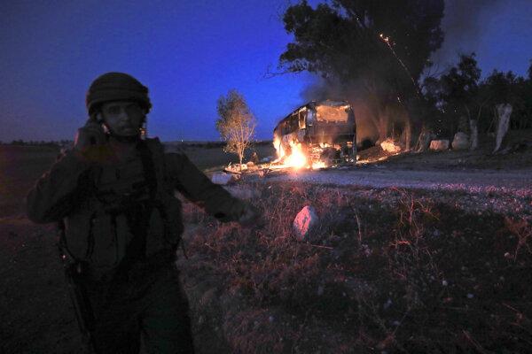 Izraelský vojak stojí pri horiacom autobuse po raketovom útoku .