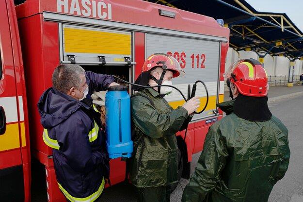 Členovia Dobrovoľného hasičského zboru v Kežmarku sa pripravujú na dezinfekciu špeciálnym prípravkom v priestoroch autobusovej stanice v Kežmarku.
