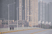Na archívnej fotografii z 28. januára 2020 kráča dvojica po opustenej ulici vo Wu-chane v čínskej provincii Chu-pej v strednej Číne.