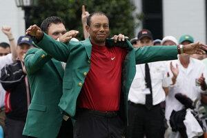 Tiger Woods si oblieka zelené sako po triumfe na Masters v Auguste 2019.