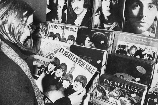 Na archívnej snímke z 10. decembra 1980 fanúšička skupiny Beatles drží v ruke v poradí štvrtý album kapely s názvom Beatles for Sale v predajni v nemeckom Stuttgarte.
