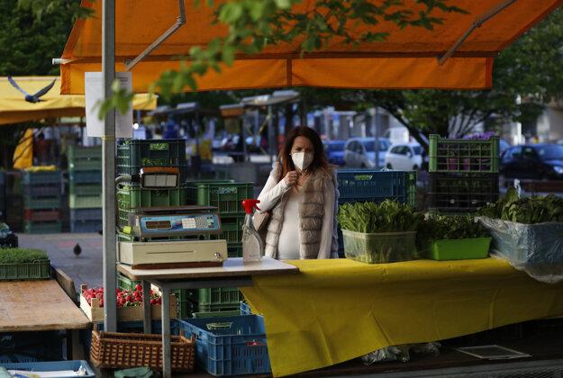 Predavačka ponúka medvedí cesnak a reďkovku na farmárskom trhu v Prahe.
