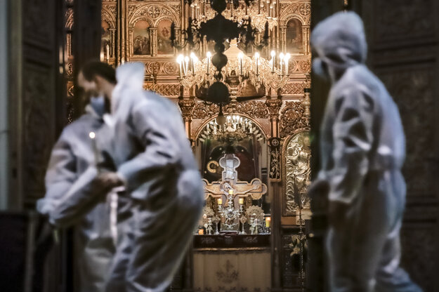 Dobrovoľníci v ochranných oblekoch pred zatvoreným kostolom v Bukurešti.
