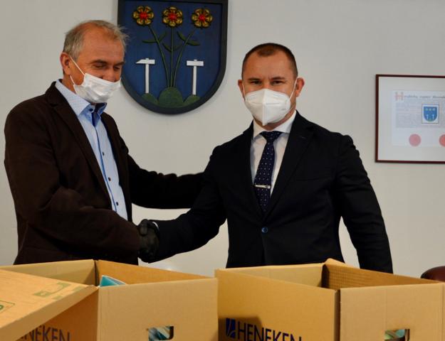 Primátor Spišskej Novej Vsi Pavol Bečarik preberá respirátory od obchodného riaditeľa Heneken, s. r. o., Adriána Stolára.