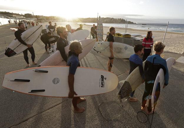 Surferi na pláži Bondi Beach v Sydney, ktorá bola pre pandémiu koronavírusu zatvorená niekoľko týždňov.