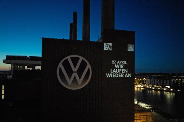 Nápis opäť začíname je vysvietený na budove teplárne s logom nemeckej automobilky Volkswagen v nemeckom meste Wolfsburg 24. apríla 2020.