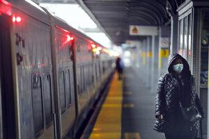 Cestujúci s ochrannými rúškami na zabránenie šíreniu nového koronavírusu vystupujú z vlaku na stanici LIRR Jamaica v štvrti Queens v New Yorku.