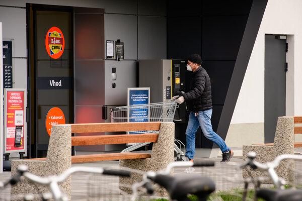 Zákazník s ochranným rúškom na tvári vstupuje do obchodu v slovinskej metropole Ľubľana.