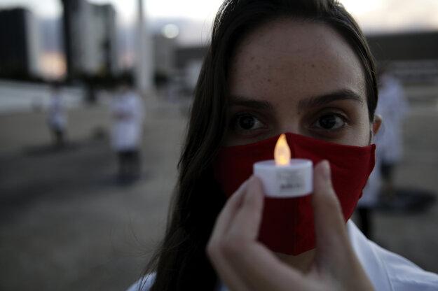 Brazílska zdravotná sestra drží sviečku na počesť svojich kolegýň, ktoré zomreli počas pandémie koronacírusu SARS-CoV-2.