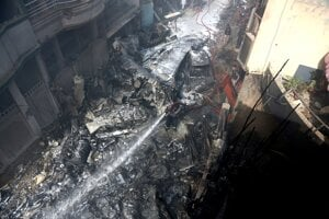 Hasiči zasahujú po zrútení dopravného lietadla spoločnosti Pakistan International Airlines v obývanej oblasti pri pakistanskom meste Karáči na juhu krajiny v piatok 22. mája 2020.