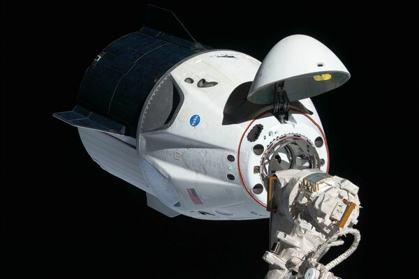 Kapsula Crew Dragon sa autonómne pripája k modulu na ISS. Vo vnútri kapsuly sú miesta na sedenie pre astronautov.