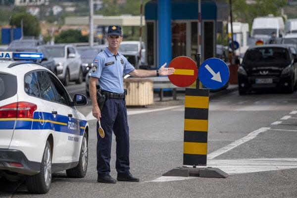 Chorvátsky policajt riadi dopravu na hraničnom priechode so Slovinskom.