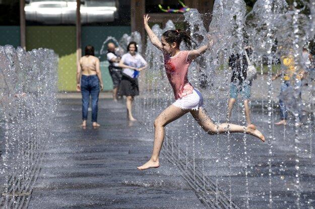 Dievča beží cez fontánu v parku pri rieke Moskva počas horúceho dňa v ruskej metropole.