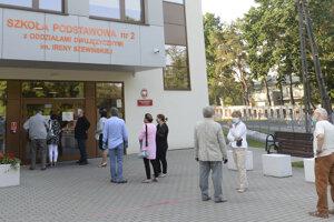 Ľudia čakajú v rade na to, aby odovzdali svoj hlas v prezidentských voľbách 2020 v Poľsku.