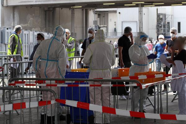 Vojaci v ochranných odevoch pomáhajú robiť skríningové testy na koronavírus v priestoroch spoločnosti Tönnies  v piatok 19. júna 2020 v meste Rheda-Wiedenbrück v spolkovej krajine Severné Porýnie-Vestfálsko.