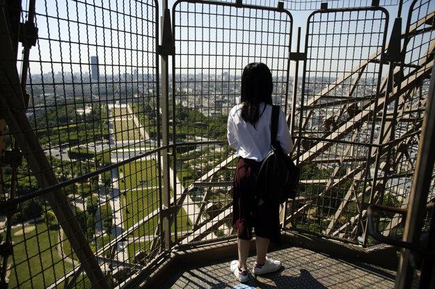 Koronavírus vo svete: Žena sa pozerá počas návštevy Eiffelovej veže v Paríži.