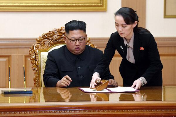 Na archívnej snímke z 19. septembra 2018 severokórejský líder Kim Čong-un a pomáha mu jeho sestra Kim Jo-Čong počas podpisu dohody na summite s juhokórejským prezidentom  Mun Če-inom v Pchjongjangu.