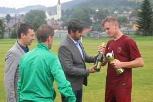 Cenu za víťazstvo vturnaji preberá kapitán Ludrovej Marko Kučera, od jedného zorganizátorov Patrika Haba.