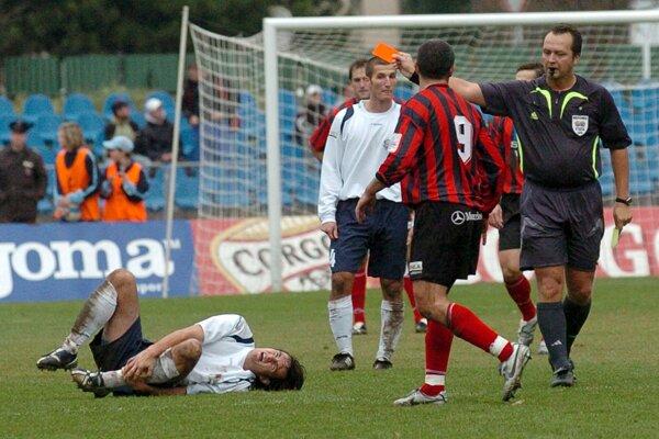 Hlavný rozhodca Pavel Olšiak (vpravo) udeľuje červenú kartu Trnavčanovi Vladimírovi Kožuchovi (č.9) po zrážke s Dubničanom Michalom Jonášom (vľavo na tráve) 25. novembra 2006 v zápase 22. kola futbalovej Corgoň ligy FK ZTS Dubnica - FC Spartak Trnava.