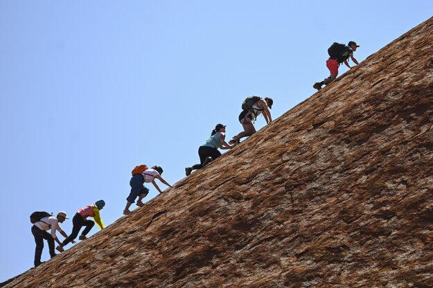 Turisti vystupujú na svetoznámy skalný útvar Uluru v strednej Austrálii.