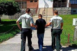 Policajti odvádzajú chyteného väzňa.