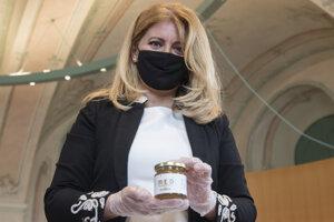 Prezidentka SR Zuzana Čaputová pózuje s pohárom medu počas prvého stáčania medu z úľov umiestnených v Prezidentskej záhrade.