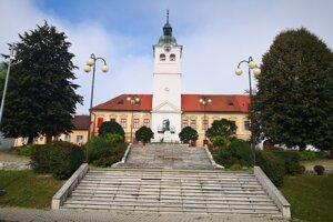 Schody vedúce na Banícke námestie v Gelnici. Pred vstupom do budovy Baníckeho múzea s bielou vežou je socha modliaceho sa baníka.
