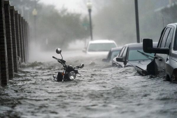 Autá a motocykel sú pod vodou, ktorá zaplavila ulicu v Pensacole na Floride po príchode hurikánu Sally v stredu 16. septembra 2020.