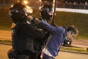 Bieloruskí policajti držia demonštranta v Minsku.